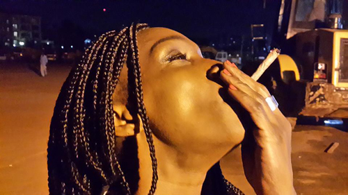 """Patra smoking the herb in between shoots. She was with the """"Ghetto President"""" so the Mary J was obviously avaiable."""